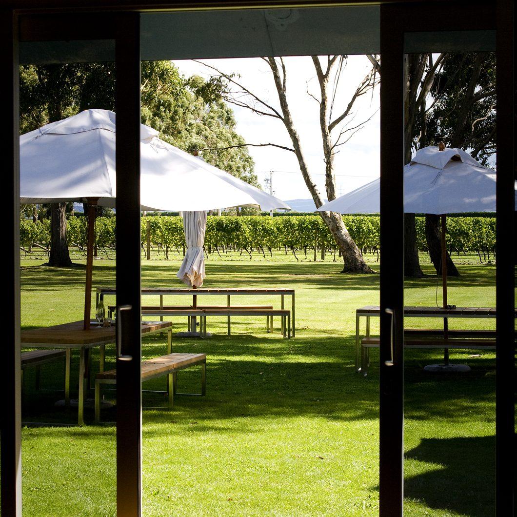 Picnic tables seen through sliding doors in sunny vineyard